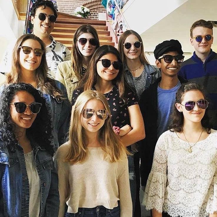 Tutors standing proudly wearing sunglasses